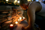 Donald Powell, 22, lights a candle as friends and family of the victims of a house fire early...