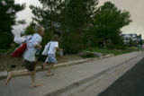 Jake Cummings, 13, left, and Ian Swartz, 10, right, run toward their homes as grass fire said to...