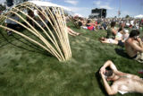Dave Cividino, 24, of Boulder, rests near bamboo structures during Mile High Music Festival at...