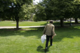 DM2009  Michael Chipps, 52, walks out of Civic Center Park with a trash bag of aluminum cans he...