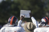 Defensive line coach Jacob Burney (cq) points out a play to Jarvis Moss (cq) (94) (left) and John...