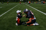 Mike Leach, tight end 83,(cq) waits for his son Ryan, 2, to tackle him after the Denver Broncos...