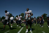 Tim Crowder, (cq) defensive end, (center) walks off the field during the Denver Broncos work out...