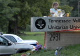A lady lays flowers and a card near the front driveway of the Tennessee Valley Unitarian...