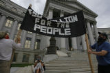 2260  Organizers from the anarchist protest group Unconventional Denver roll out a banner that...