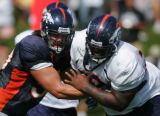 Marcus Thomas, right, goes against bn Hamilton, left, during Broncos training camp in Dove Valley...