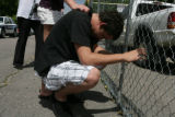 Weston Hyde, 20 (cq) kneals in front of a chain link fence set up outside 9876 Fairwood St., in...