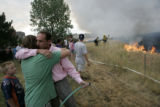 Mike Swartz hugs his son Sam as a grass fire said to be started by lightning spreads over Green...