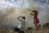 Ann Catanzaro, left, watches a wilfire with her granddaughter Jessica Diagle, 10, said to be...
