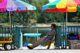 Zech Papp, (cq) sits in the shade of a umbrella to get out of the heat, while waiting for people...