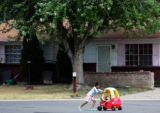 Elizabeth Harris, 5, pushes her neighbor Demora Nave, 3, in the Montbello neighborhood which has...