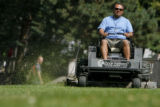 3146  Jose Palma, operations supervisor for Civic Center Park, speeds along as he mows a section...