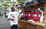 Adam Ouedraoga (cq) sells hats at his stand, ETS Adou, on the 16th Street mall at Welton Street...