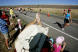 Hank Kinnie, of Denver, claps for his wife, Leslie as she runs by in the fifth annual Tri for the...