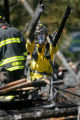 Firefighters with West Metro Fire and Rescue sift through the burned out remains of a house that...