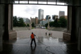 A Civic Center Park worker uses a power washer to spray off pigeon poop from the Greek Theater in...