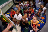 (784) Kindergartners listen as Thelma Hood reads a story during the first day of school at...