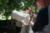 David Anderson, left, adds milled malted barley to a barrel of heated water, while Christopher...