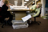 Marilyn Mohling, (cq) a temporary election worker sets a ballot aside to be faxed Thursday,...
