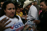 Graciela Cabral (left) (cq) works to register new voters as Raul Chaves listens (cross, at right)...