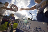 (012)  A Pedal to Properties real estate agent Chris Cullen hands a bike helmet to one of his...