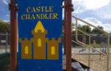 (048)  Passerbyes walk by a playground structure named Castle Chandler, in honor of Chandler...