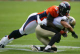 D.J. Williams tackles Robert Meachem in the first quarter of the Denver Broncos against the New...