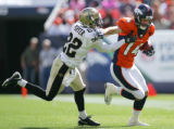 Tracy Porter tries to tackle Brandon Stokely in the first quarter of the Denver Broncos against...