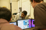 Suman Anand, 36, (cq) leans over to look at a computer while Rahul Trivedi, 24, (left) (cq) and...