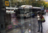 Pedestrians walk past a Washington Mutual branch at the 16th Street Mall in Denver, a day after...