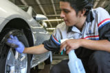 Miguel Montes (cq) cleans a tire of a 2008 Impala LT, Tuesday afternoon, at Len Lyall Chevrolet,...