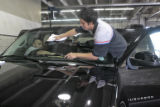 Jose Martinez (cq), left, and Miguel Montes (cq) clean the windshield of a 2008 Suburban,Tuesday...