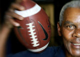 Former Broncos quarterback Marlin Briscoe is photographed alongside a football at the...