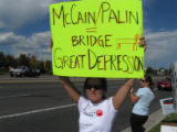 Cutline: Jessica Yates, 37, of Boulder waves an anti Sarah Palin sign Sunday at one of two rallies...