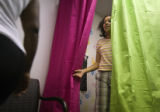 (055) Amona Rosales, 11, of Denver, peaks out a fitting room as she shops for new clothes Sunday,...