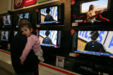 Vaneessa Domingues, 2 rest on her dad's Efren Domingues shoulder as he shops for an HD TV at...
