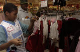 (DENVER, Colo., December 23, 2004) Andre Retland,11, looks for dresses for his sister wtih help...