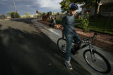 D'Artagnan Dye sits on his bike with his dad Larry Dye standing by  their home in Commerce City,...
