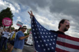 (DENVER, CO. 6/1/04) Anti-Bush protester Dean Nye hold an American flag at the corner of...