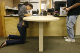 Lisa Wax, 22, kneels to finish filling out her form as she changes her address for her voter...