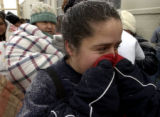 (Denver, Colo., Dec. 23, 2004) Isida Ortega uses her coat sleeves to warm her face while waiting...