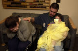 Diego Huckabay leans against his father, Brian Huckabay, as his mother Janelle Portillis cries at...