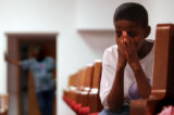 (Denver, Colo., June 2, 2004) Dupree Carter, 11, lowers his head during a prayer at a town hall...