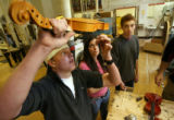 MJM303   Matt Gosche (cq), 17, left, tries to get a soundpost out of a violin as Sara Sims (cq),...