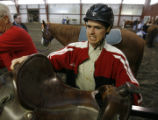 DM0015  Michael Meeks, 24, grabs the saddle for the horse is going to ride at the Praying Hands...