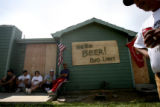 ({seqn)} Family members and neighbors of Hugo Flores (right) wait outside his house for someone to...