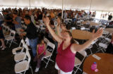 DM1088  Michelle Piatt raises her hands in praise as she attends an outdoor church service for The...