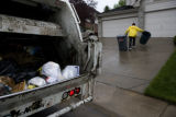 Johnnie Arguello (cq) a garbageman for Pro Disposal hustles trash cans up a driveway in...