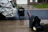 Johnnie Arguello (cq) a garbageman for Pro Disposal lifts a trash can into a garbage truck in...