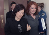 Christine Wolfe, left, is lead out of the courtroom by Ann B. Tomsic (cq), Chief Deputy District...
